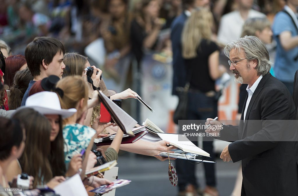 US director Gore Verbinski (R) signs autographs as he arrives for the premiere of the film 'Lone Ranger' on July 19, 2013 in Berlin. The film will start in German cinemas on August 8, 2013.