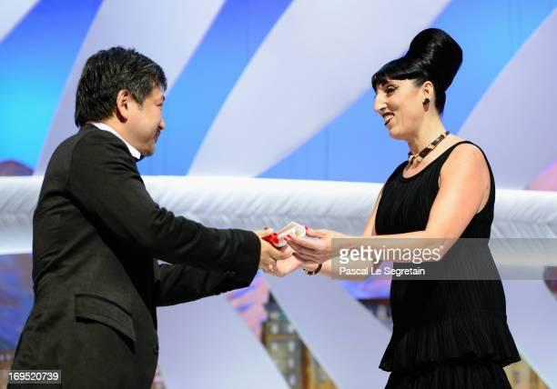 Director Hirokazu Koreeda receives the Prix Du Jury for 'Soshite Chichi Ni Naru' from actress Rossy de Palma at the Inside Closing Ceremony during...