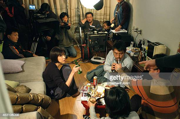 Director Hong SangSoo far corner with glasses directs leading male actor Kim Taewoo and leading actress Sung Hyunah during the shooting of 'Woman is...
