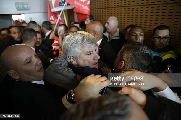 Director in charge of human resources of Air France longhaul flights Pierre Plissonnier is led away from demonstrators by security officers after...