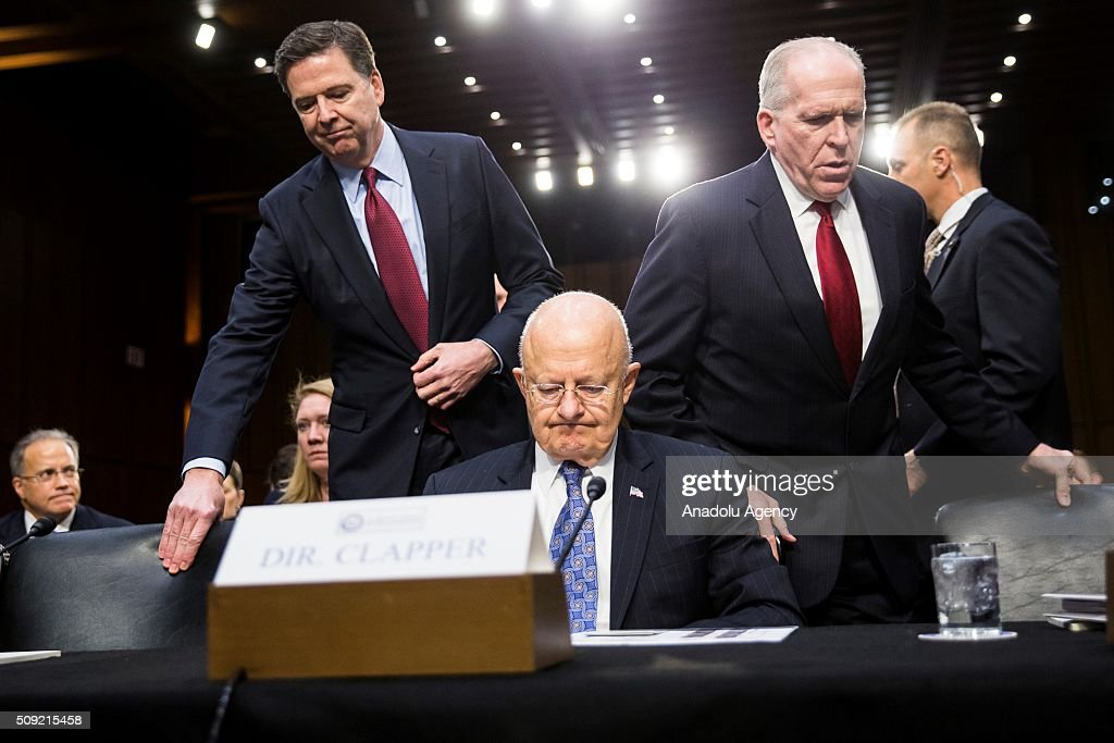 FBI Director James Comey (L) and CIA Director John Brennan (R) take their seats flanking National Intelligence Director James Clapper during a Senate Intelligence Committee hearing in Washington, USA on February 9, 2016.