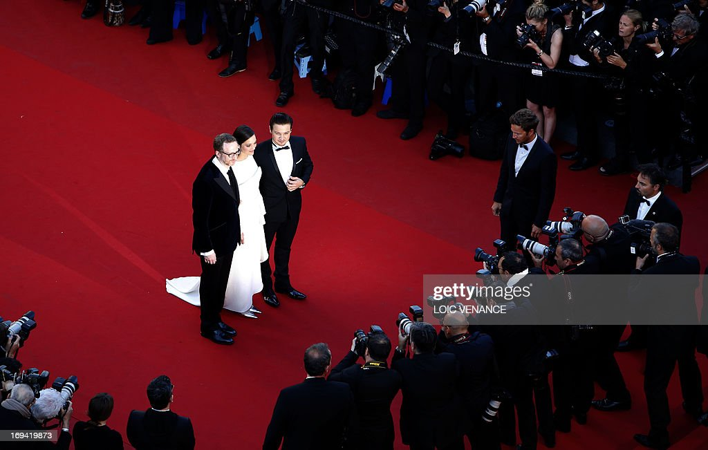 US director James Gray, French actress Marion Cotillard and US actor Jeremy Renner pose on May 24, 2013 as they arrive for the screening of the film 'The Immigrant' presented in Competition at the 66th edition of the Cannes Film Festival in Cannes. Cannes, one of the world's top film festivals, opened on May 15 and will climax on May 26 with awards selected by a jury headed this year by Hollywood legend Steven Spielberg. AFP PHOTO / LOIC VENANCE