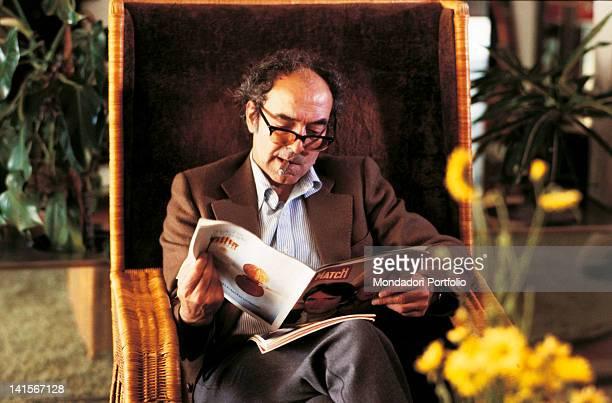 Director Jean Luc Godard reading a magazine sitting on a wicker chair smoking a cigar 1983