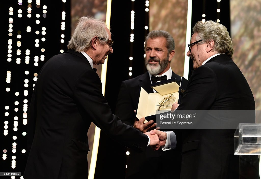 Director Ken Loach is congratulated by Mel Gibson and director and President of the Jury George Miller after being awarded the Palme d'Or for the...