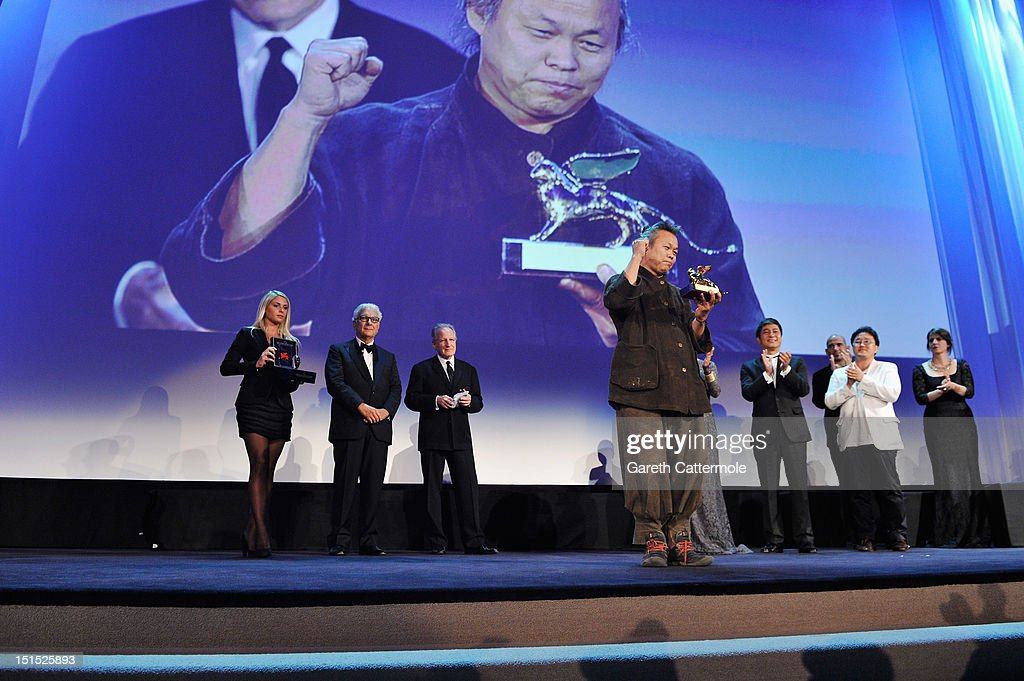 Director <a gi-track='captionPersonalityLinkClicked' href=/galleries/search?phrase=Kim+Ki-Duk&family=editorial&specificpeople=2212557 ng-click='$event.stopPropagation()'>Kim Ki-Duk</a> wins the Golden Lion for best film award on stage during the Award Ceremony at the 69th Venice Film Festival at the Palazzo del Cinema on September 8, 2012 in Venice, Italy.