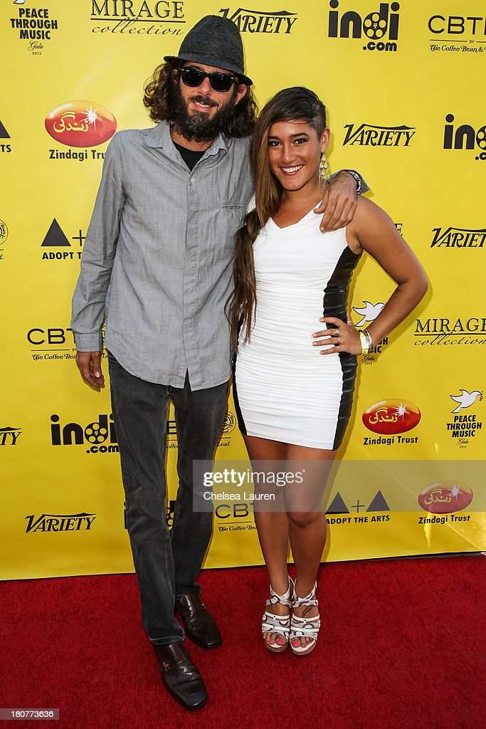 Director Lincoln O'Barry (L) and actress Q'orianka Kilcher arrive at Adopt the Arts' Peace Through Music celebrity gala at Loews Hollywood Hotel on September 15, 2013 in Hollywood, California.