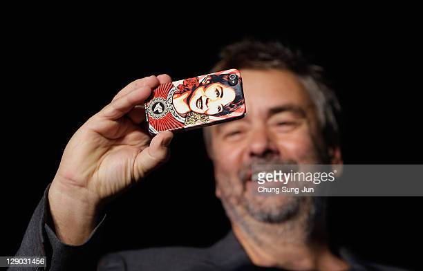 Director Luc Besson takes a picture with his mobile phone is attached Burmese democracy icon Aung San Suu Kyi's photo during his Hand Printing event...