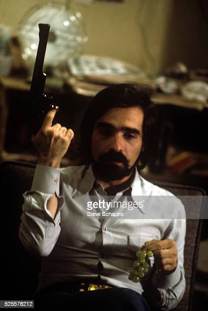 Director Martin Scorcese is shown holding a gun and a bunch of grapes during the shooting of Taxi Driver