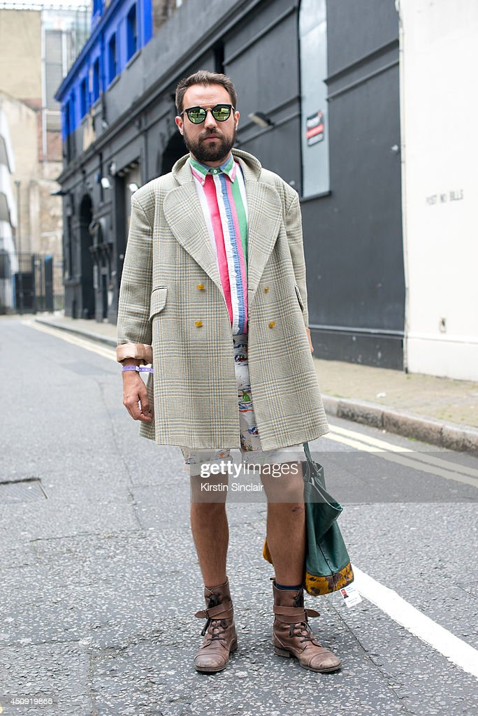 TV director Maurizio Von Trapp wears a Vivienne Westwood coat, Ralph Lauren shirt, Jazz and B bag, Office boots, Topman sunglasses and Henchman shorts on day 2 of London Collections: Men on June 16, 2014 in London, England.
