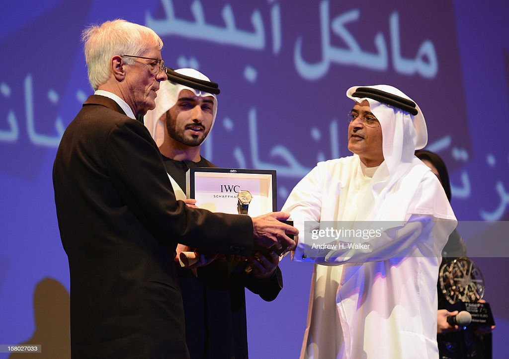 Director Michael Apted receives a IWC watch, as part of the Lifetime Achievement award presentation by Sheikh Mansour bin Mohammed bin Rashid al-Maktoum and DIFF Chairman Abdulhamid Juma at the Opening Ceremony during day one of the 9th Annual Dubai International Film Festival held at the Madinat Jumeriah Complex on December 9, 2012 in Dubai, United Arab Emirates.