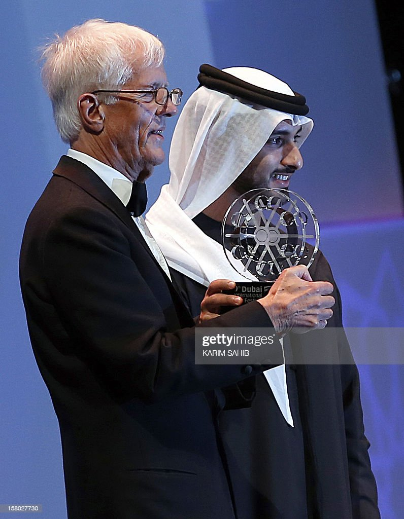 Director Michael Apted receives a IWC watch, as part of the Lifetime Achievement award presentated by Sheikh Mansur bin Mohammed bin Rashid al-Maktoum during the opening ceremony of the Dubai International Film Festival in the Gulf emirate of Dubai, on December 9, 2012. AFP PHOTO/KARIM SAHIB