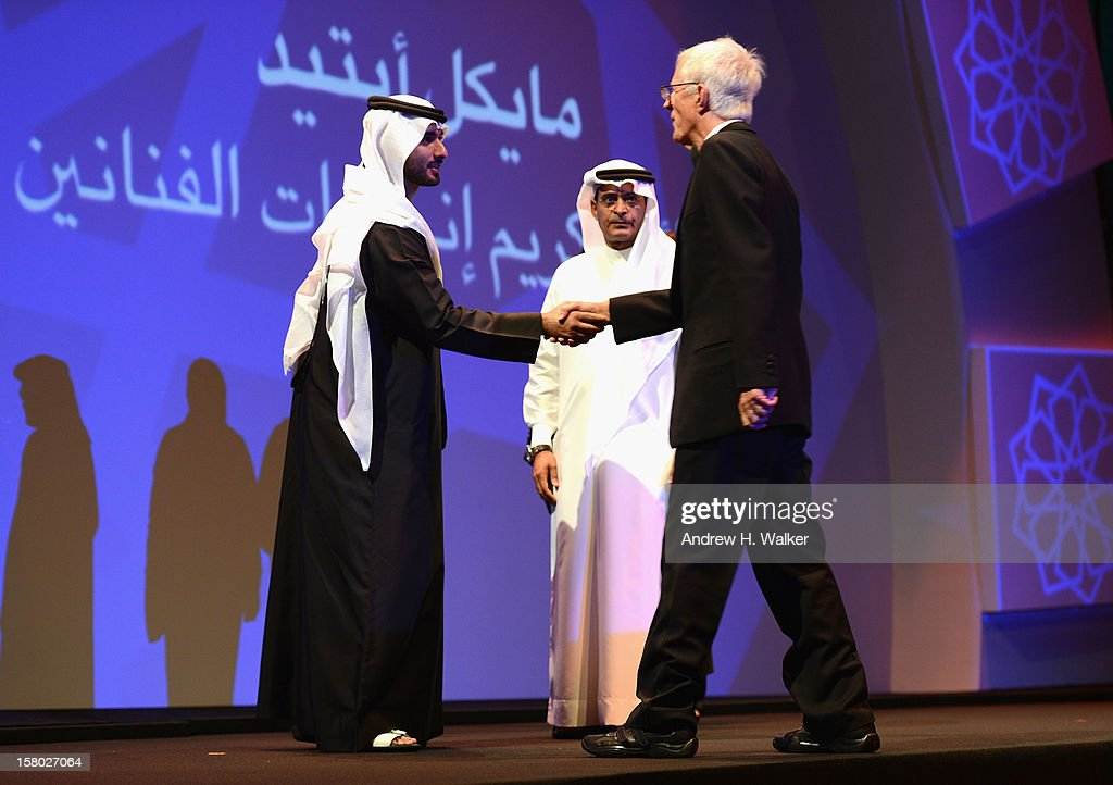 Director Michael Apted shakes hands with Sheikh Mansour bin Mohammed bin Rashid al-Maktoum as DIFF Chairman Abdulhamid Juma looks on at the Opening Ceremony during day one of the 9th Annual Dubai International Film Festival held at the Madinat Jumeriah Complex on December 9, 2012 in Dubai, United Arab Emirates.