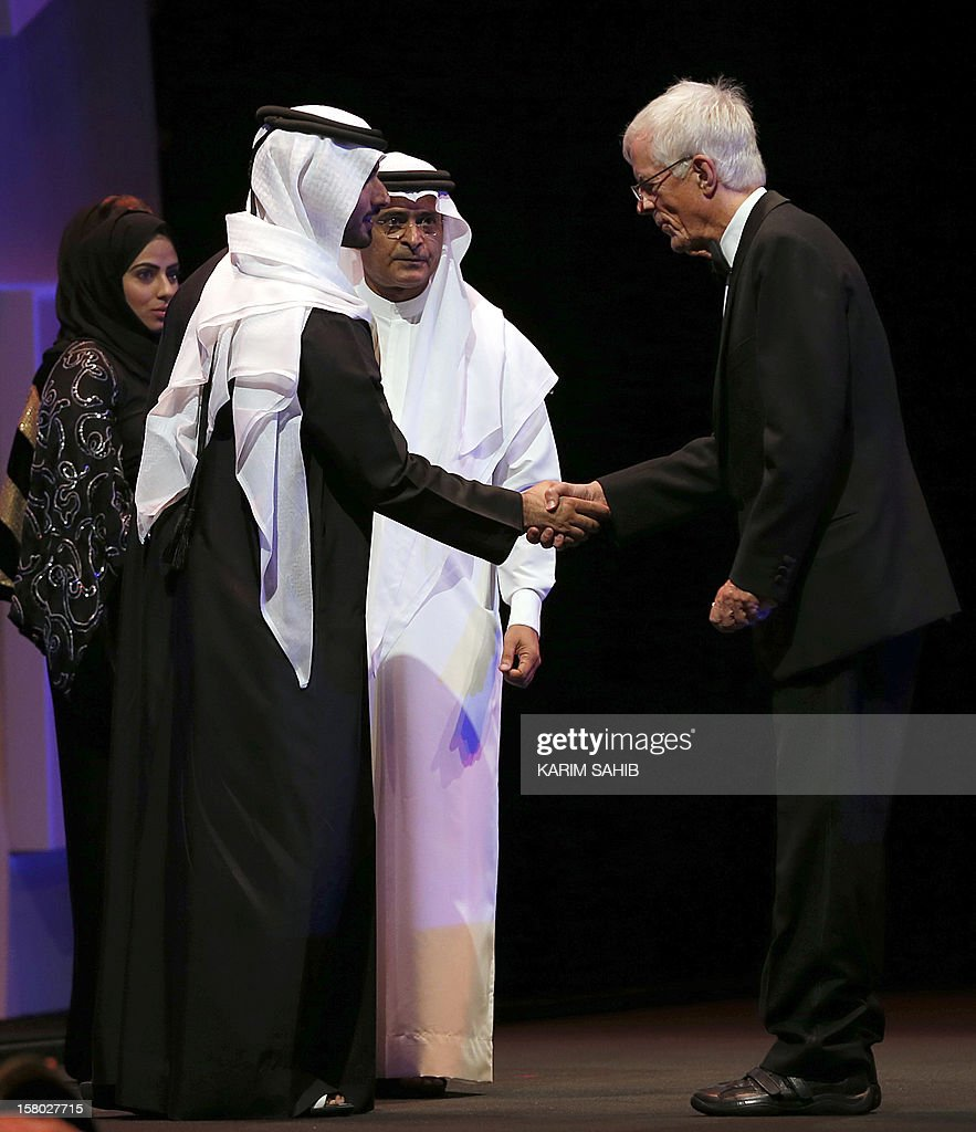 Director Michael Apted shakes hands with Sheikh Mansour bin Mohammed bin Rashid al-Maktoum during the opening ceremony of the Dubai International Film Festival in the Gulf emirate of Dubai on December 9, 2012.