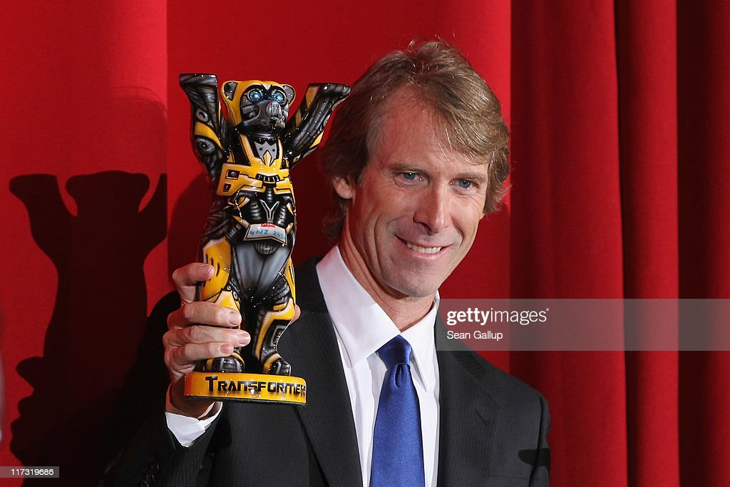 Director Michael Bay holds a Berlin bear sculpture that looks like a Transformer as he attends the 'Transformers 3' European premiere on June 25 2011...