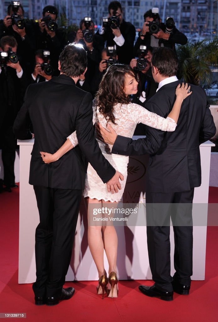Director Michel Hazanavicius, actress Berenice Bejo and Jean Dujardin after he receives the Award for Best Actor for the film 'The Artist' during the Palme D'Or Winners Photocall at the 64th Annual Cannes Film Festival at the Palais des Festivals on May 22, 2011 in Cannes, France.