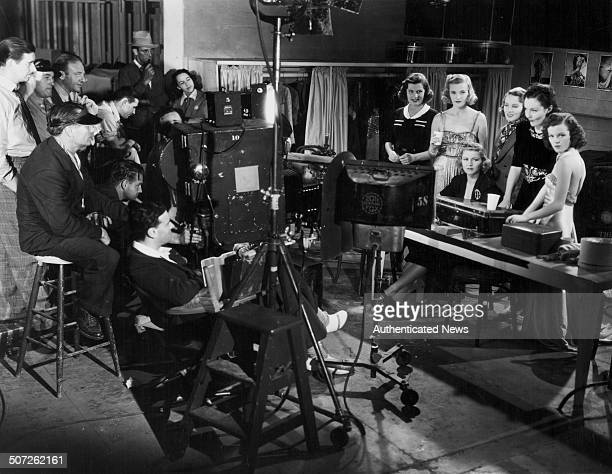 Director Norman Foster sitting behind a film camera with his crew on the set of the movie 'Walking Down Broadway' with actresses Leah Ray Phyllis...