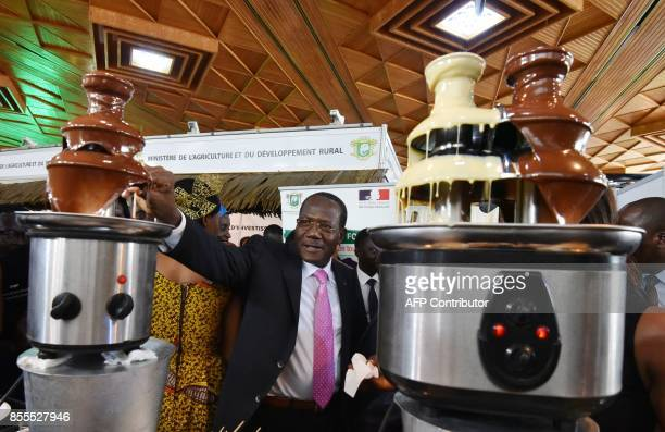 Director of Cabinet of Ivory Coast's Ministry of Agriculture Coulibaly Siaka dips into a chocolate fountain at a cocoa and chocolate stand on...