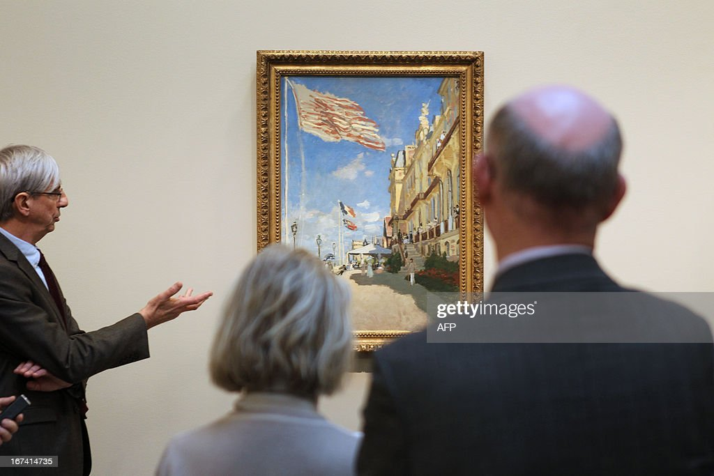 Director of Caen's fine arts museum, Patrick Ramade (L) looks at the painting 'L'hotel des Roches Noires à Trouville' of Claude Monet, three days before the opening of 'Normandie Impressionniste' at Caen's fine arts museum, on April 24, 2013. The exhibition which takes place in Caen is one of the three most important, with the ones of Le Havre and Rouen, which are 'National interest' labelized. Caen's exhibition gathers 67 art paintings including 34 from abroad. This exhibition (in Rouen, Caen and Le Havre) begins on April 27 to September 29. AFP PHOTO CHARLY TRIBALLEAU