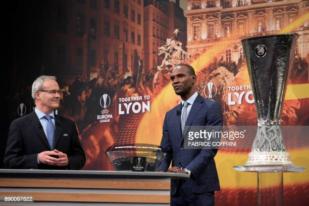 UEFA director of competitions Giorgio Marchetti and French former international Eric Abidal speak flanked by the Champions League trophy ahead of...