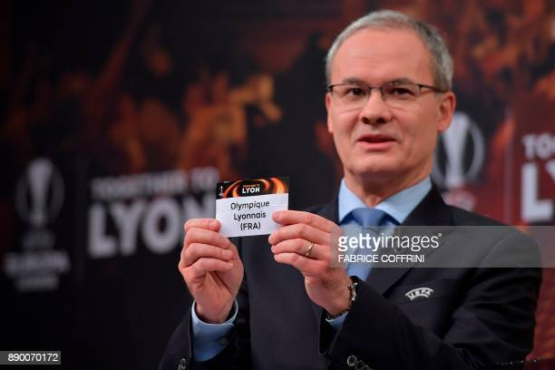 UEFA director of competitions Giorgio Marchetti shows the slip of Olympique Lyonnais during the draw for the round of 32 of the UEFA Europa League...