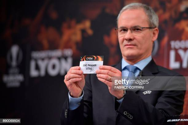 UEFA director of competitions Giorgio Marchetti shows the slip of SSC Napoli during the draw for the round of 32 of the UEFA Europa League football...
