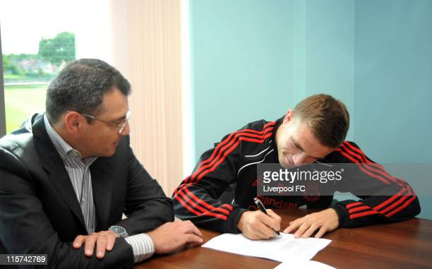 Director of Football for Liverpool Damien Comolli sits by Jordan Henderson as he signs for Liverpool FC at Melwood Training Ground on June 8 2011 in...