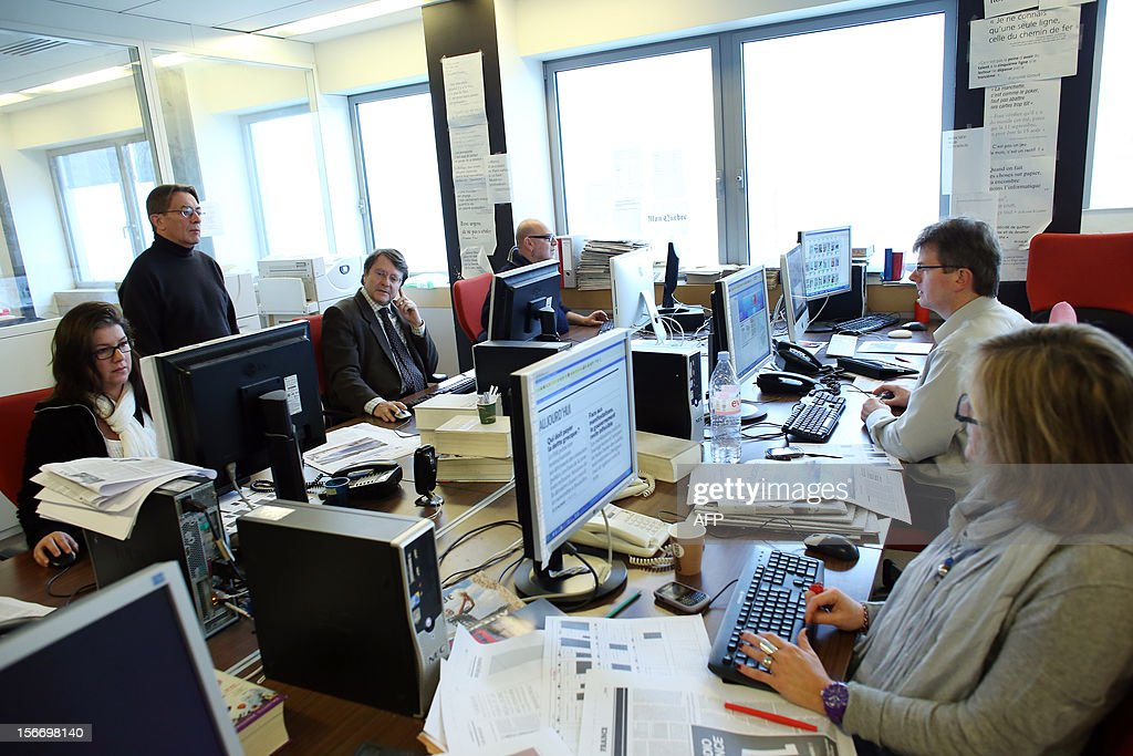 Director of French daily newspaper Le Monde, Erik Izraelewicz, (3L) looks at a computer screen on November 19, 2012 in Paris during the close of deadlines for the day's edition. Le Monde today unveils a new layout of the newspaper. AFP PHOTO THOMAS SAMSON