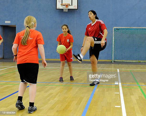 Director of German Football Association Steffi Jones plays with pupils during the visit of EllyHeuss School on November 9 2011 in Wiesbaden Germany