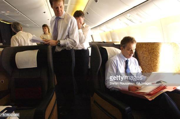 Director of Government Communications Alastair Campbell looks on as British prime Minister Tony Blair studies papers en route to the Azores where the...