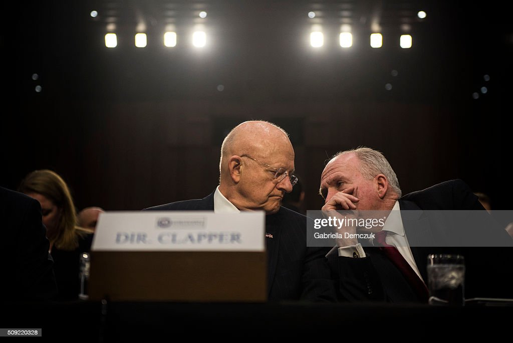Director of National Intelligence James Clapper speaks to CIA Director John Brennan before the start of the Senate (Select) Intelligence Committee hearing at the Hart Senate Building on February 9, 2016 in Washington, D.C. The committee met to hear testimony about worldwide threats to America and its allies.