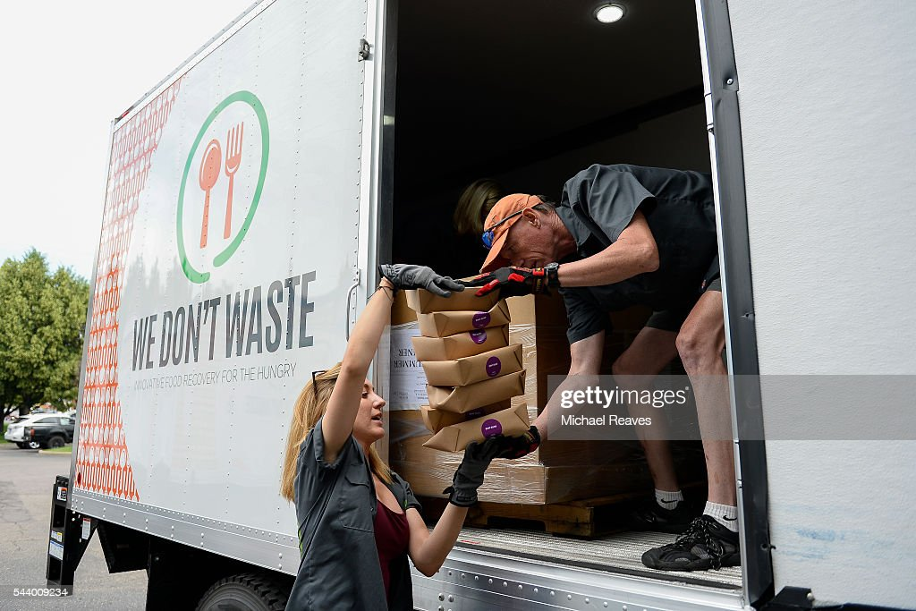 Director of operations Tim Sanford hands a stack of boxes of buns Morgan Gergenbach to deliver to There with Care on June 30, 2016.