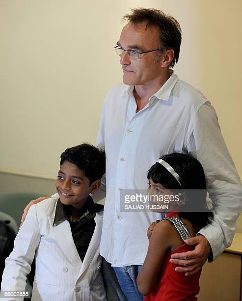 Director of Oscar winning movie 'Slumdog Millionaire' Danny Boyle poses with the two child stars of the film Mohammad Azharuddin and Rubina Ali after...