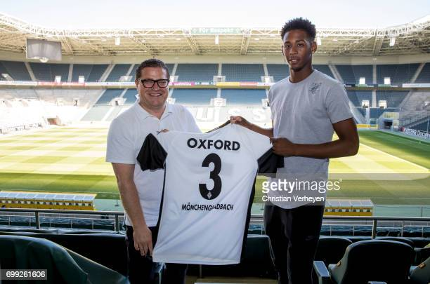 Director of Sport Max Eberl and Reece Oxford pose with his new shirt after he signs a seasonlong loan deal contract with Borussia Moenchengladbach at...