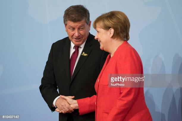 Director of the International Labour Organization Guy Ryder is welcomed by German Chancellor Angela Merkel prior to a first meeting of G20 leaders at...
