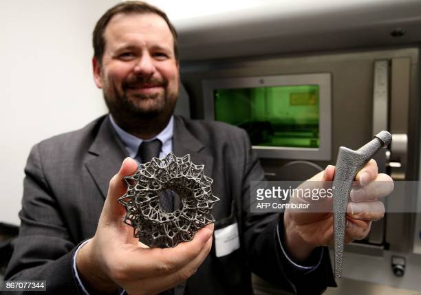 Director of the Platinium 3D scientific and technology platform Sebastien Guenet shows a complex metallic 3Dprinted part and 3Dprinted metal femoral...