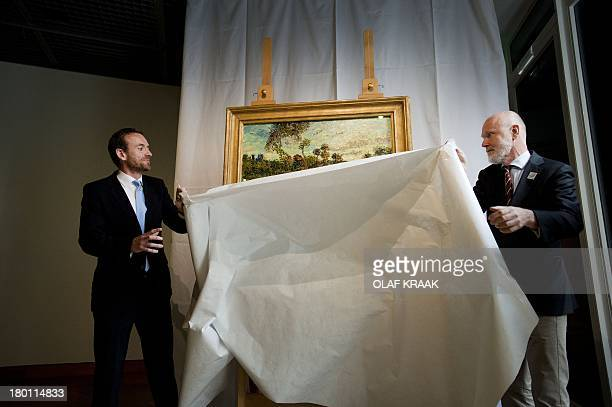 Director of the Van Gogh Museum in Amsterdam Alex Ruger and researcher Louis van Tilbourgh unveil a painting by Vincent van Gogh entitled 'Sunset at...