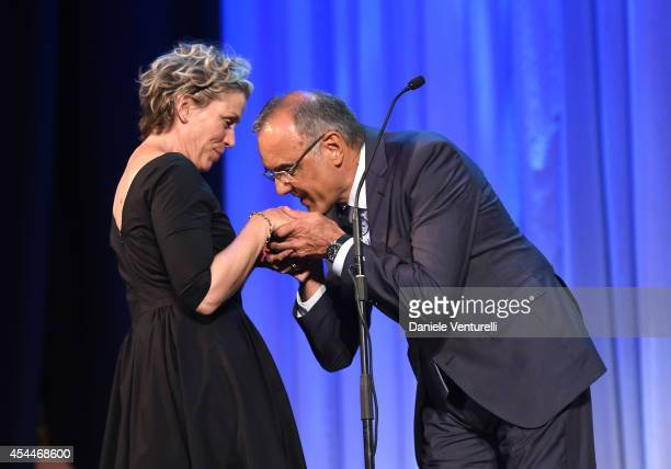 Director of the Venice Film Festival Alberto Barbera kisses Frances McDomand's hand as she is awarded the 2014 Persol tribute to visionary talent...