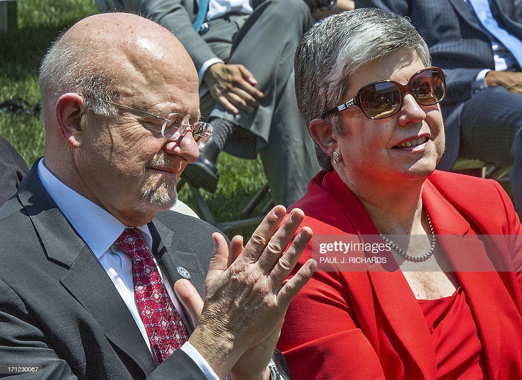 Director of US National Intelligence James Clapper (L) and Homeland Security Director Janet Napolitano (R) share a few words before US President Barack Obama speaks in the Rose Garden at the White House in Washington on June 21, 2013 to announce his nomination of Jim Comey to be the next director of the Federal Bureau of Investigations (FBI). Comey, a deputy attorney general under George W. Bush, would replace Robert Mueller, who is stepping down from the agency he has led since the week before the September 11, 2001 attacks. AFP PHOTO/Paul J. Richards