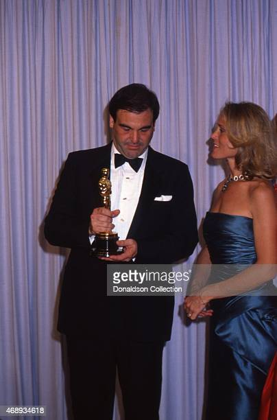 Director Oliver Stone and his wife Elizabeth Burkit Cox at Academy Awards in March 1987 in Los Angeles California