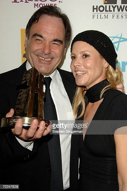 Director Oliver Stone winner of Director of the Year poses with actress Maria Bello poses in the press room at The Hollywood Film Festival 10th...