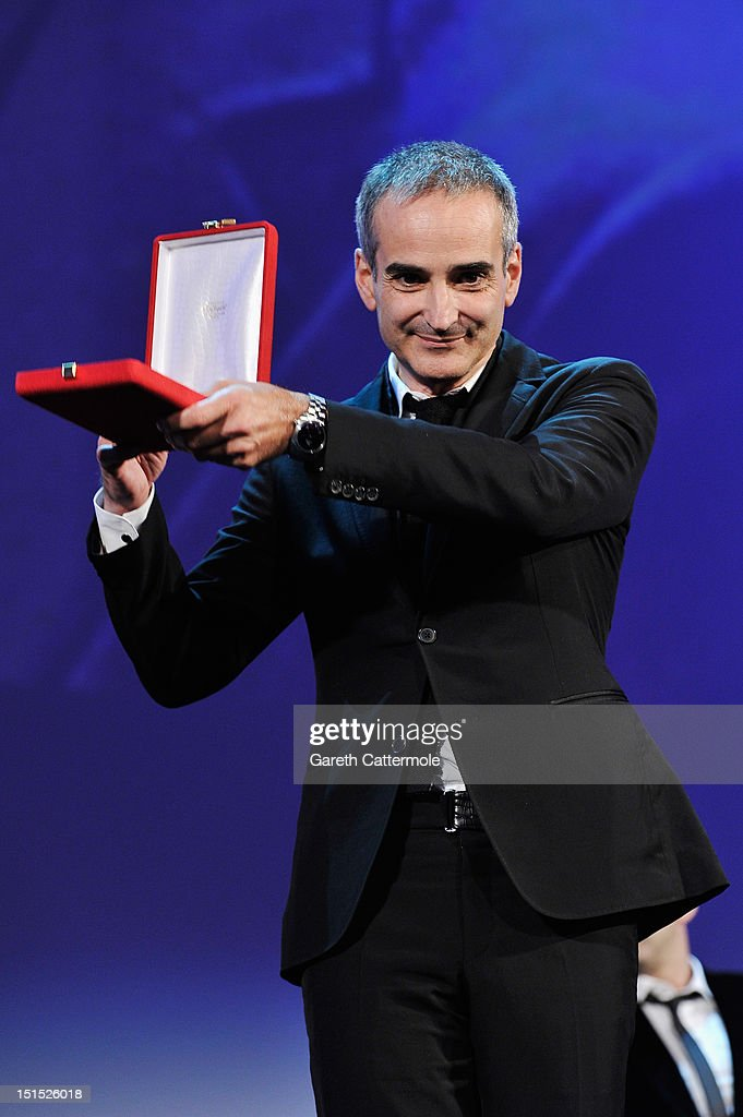 Director <a gi-track='captionPersonalityLinkClicked' href=/galleries/search?phrase=Olivier+Assayas&family=editorial&specificpeople=240407 ng-click='$event.stopPropagation()'>Olivier Assayas</a> with his award for Best Screenplay for the film 'Apres Mai' on stage during the Award Ceremony at the 69th Venice Film Festival at the Palazzo del Cinema on September 8, 2012 in Venice, Italy.