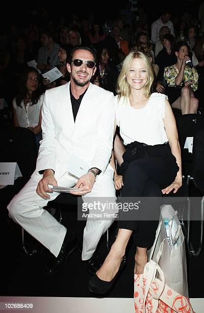 Director Oskar Roehler and actress Heike Makatsch pose in front row at the Kaviar Gauche Show during the Mercedes Benz Fashion Week Spring/Summer...