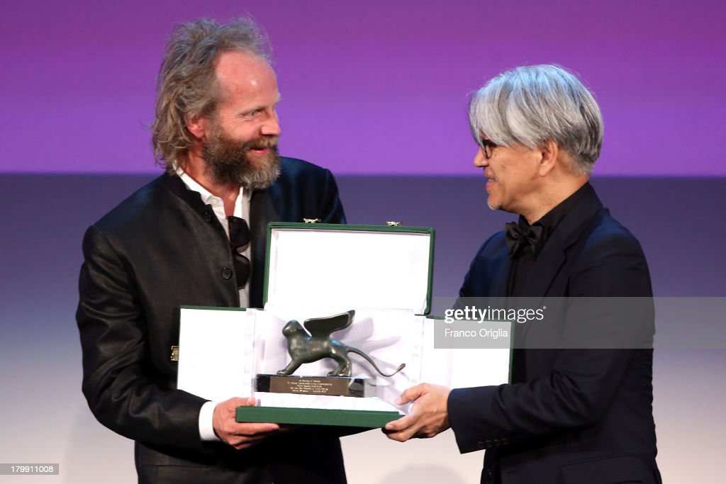 Director Philip Groning receives from producer <a gi-track='captionPersonalityLinkClicked' href=/galleries/search?phrase=Ryuichi+Sakamoto&family=editorial&specificpeople=790311 ng-click='$event.stopPropagation()'>Ryuichi Sakamoto</a> the Special Jury Prize Award for his movie 'Die Frau Des Polizisten' as he attends the Closing Ceremony during the 70th Venice International Film Festival at the Palazzo del Cinema on September 7, 2013 in Venice, Italy.