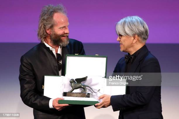Director Philip Groning receives from producer Ryuichi Sakamoto the Special Jury Prize Award for his movie 'Die Frau Des Polizisten' as he attends...