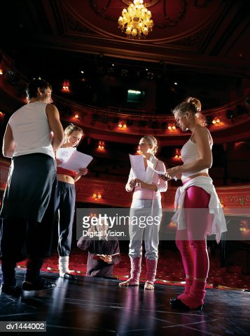 Director Pointing to a Group of Performers Rehearsing on Stage