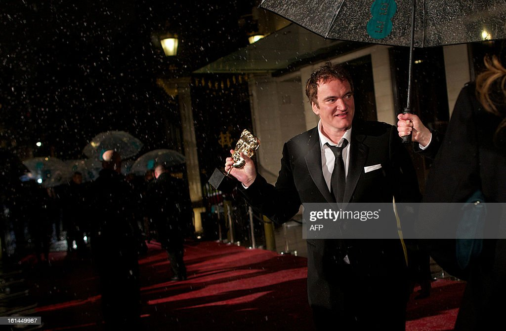 US director Quentin Tarantino holds his award for best original screenplay as he arrives for the BAFTA British Academy Film Awards after party in London on February 10, 2013.