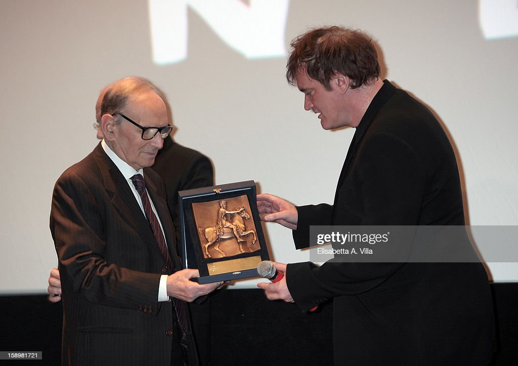 Director <a gi-track='captionPersonalityLinkClicked' href=/galleries/search?phrase=Quentin+Tarantino&family=editorial&specificpeople=171796 ng-click='$event.stopPropagation()'>Quentin Tarantino</a> (R) receives Rome Film Festival Lifetime Achievement Award from Italian composer <a gi-track='captionPersonalityLinkClicked' href=/galleries/search?phrase=Ennio+Morricone&family=editorial&specificpeople=677347 ng-click='$event.stopPropagation()'>Ennio Morricone</a> at Cinema Adriano on January 4, 2013 in Rome, Italy.