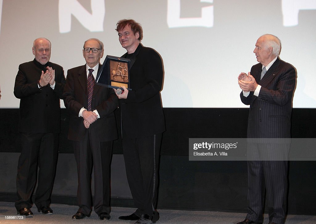Director <a gi-track='captionPersonalityLinkClicked' href=/galleries/search?phrase=Quentin+Tarantino&family=editorial&specificpeople=171796 ng-click='$event.stopPropagation()'>Quentin Tarantino</a> receives Rome Film Festival Lifetime Achievement Award from Italian composer <a gi-track='captionPersonalityLinkClicked' href=/galleries/search?phrase=Ennio+Morricone&family=editorial&specificpeople=677347 ng-click='$event.stopPropagation()'>Ennio Morricone</a> (2nd L), Marco Muller (L) and Paolo Ferrari (R) at Cinema Adriano on January 4, 2013 in Rome, Italy.