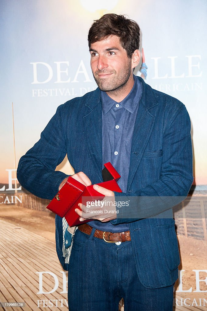 Director Sam Fleischner poses with his award for his film 'Stand clear of the closing doors' during the 39th Deauville American Film Festival on September 7, 2013 in Deauville, France.