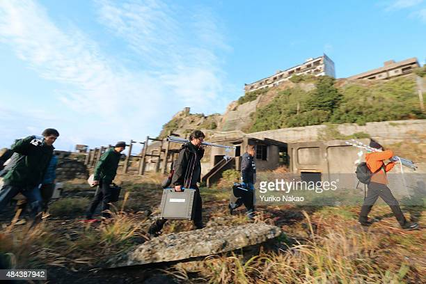 Director Shinji Higuchi carries equipments along with his staffs during a location hunting for his film 'Attack on Titan' on Hashima Island commonly...